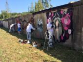 Молодые художники расписывают стену гаражей у будущей велодорожки во Всеволожске
